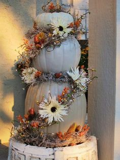 Always had a preference for white pumpkins.  Make a three-tiered topiary like this with fall leaves, berries, etc for Autumn. Then, transition to winter by removing the extras and dressing the pumpkins up like a snowman.  Maximize the life of your pumpkins!  (If you don't care for white pumpkins in the fall, use regular ones for the topiary, and then paint them white for your snowman.)