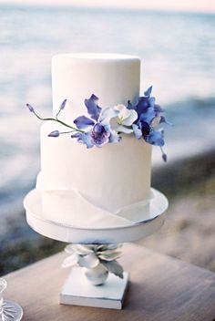Two tier wedding cake with lavender flower accents: http://www.stylemepretty.com/2016/09/11/this-ethereal-seaside-inspiration-is-purple-with-a-purpose/ Photography: Kurtz Orpia - http://www.kurtzorpia.ca/