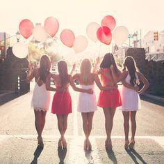 Chicas sosteniendo globos mientras caminan por la carretera