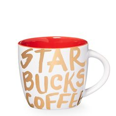 A white ceramic demitasse mug with gold graffiti-style letters and a red interior.