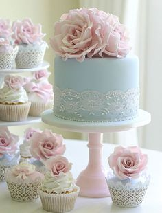 Pastel cake with matching rose topped cupcakes in pastel pink, blue, yellow with lace paper.
