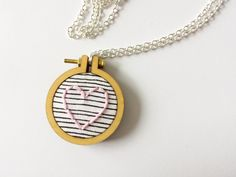 Heart Stripe Embroidery Hoop Necklace    Hand embroidered embroidery hoop necklace featuring a pink heart stitched on striped fabric. The pendant