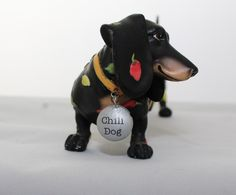This difficult to find Hot Diggity - Chili Dog Figurine #16504 was made and distributed in 2005 by Westland Giftware. The figurine is a whimsical artistic creation blended with the image of a Dachshun