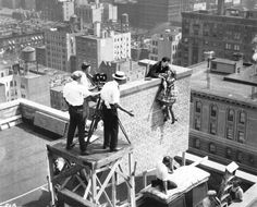 """From a lost movie serial from 1925 called """"Play Ball."""" The man in the straw hat was the director, Spencer Gordon Bennett, and the two stars are most likely Walter Miller and Allene Ray.   An exterior building set was erected on top of an actual office building near Main Street near 5th. The purpose of this was to create an illusion of height and to provide safety for the cast and crew; however, judging from the real life ledge nearby, this stunt was still dangerous enough. Bizarre Los…"""