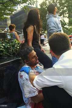 An injured civilian is treated as a tower of the World Trade Center collapses September 11, 2001
