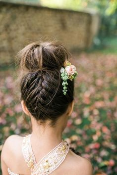 Flower girl updo: Bun with a french braid in the back and floral hair accessories for an elegant garden wedding.