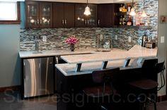 Basement bar with two-tiered granite countertop, blue glass tile backsplash and kegerator | Sun Design Inc.
