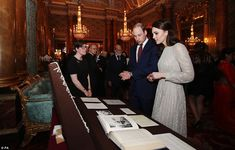 Family history: The Royal couple looked at the shawl, seen hanging up on display, while lo...