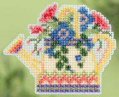 Watering Can is the title of this cross stitch kit from Mill Hill Designs. The kit includes beads, treasures, perforated paper, magnet, floss, needles, chart and instructions.