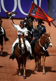 San Francisco Giants' pitcher Madison Bumgarner (40) carries the World Series banner so it can be flown during Opening Day pre-game ceremonies as they host the  Rockies for the first of three games at AT&T Park in San Francisco, Calif., Monday, April 12, 2015. (Patrick Tehan/Bay Area News Group)