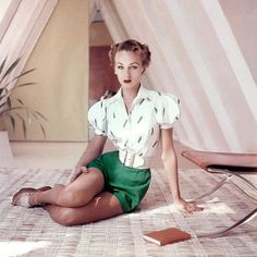 Model wearing green shorts, white cotton shirt embroidered with pea pods and a wide, cinched belt, 1952. Photo by Frances McLaughlin-Gill.