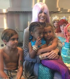 Celebration: Khloe Kardashian in a light purple wig embraced her nieces North West and Penelope Disick who were dressed as mermaids for their joint birthday party held on Saturday. Also pictured is Mason Disick, six