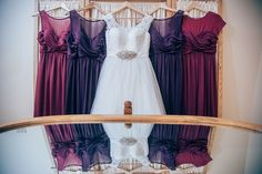 Ivory A line wedding dress with large lace bust and sleeve detail, tulle skirt and sash brooch sewn into waist. Berry themed bridesmaids dresses. Colors are plum and sangria.