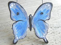 A striking butterfly, this Blue is handcrafted in salt dough, painted in shades of blue with black trim and white markings for a very realistic butterfly captured in dough! Metallic blue paint creates