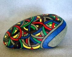 This is OOAK, one-of-a-kind abstract art work. This will make a fantastic home decor art piece or a cool conversation piece for your office decor. If you are looking for the perfect gift for someone who has everything this is it! This is a large oval river rock that I have created into a unique 3-d work of art. The painted rock has a black background with streamers of rainbow colors on both sides. It can be rotated in different directions to present a variety of faces, as your mood dictates…