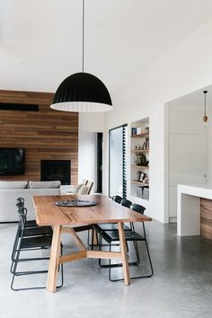 Wood accent wall, white walls and concrete floors   Contemporary Dining Room by Altereco Design