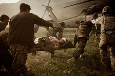 AFGHANISTAN. Kunar Province. March 2010. Afghan soldiers carry a wounded comrade into an American medevac helicopter after a Taliban ambush near the village of Tsunek, Kunar Province. – Magnum Photos – Moises Saman