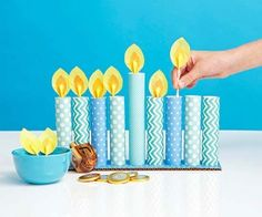Cover a 3- by 12-inch piece of corrugated cardboard with scrapbook paper. Roll and tape 8 paper rectangles to form tubes. Dip one end of each tube in tacky glue and place tubes on the base. For each flame, cut a teardrop shape from orange card stock and a slightly larger teardrop from yellow tissue paper. Cover the orange piece with glue then place a cotton swab on top. Smooth the tissue paper over the orange paper and swab and let dry.