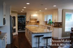 This kitchen remodel features light cabinets and light counter-tops with a darker flooring!