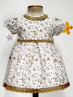 Vestido para bebe niña en micropana beige con flores en camel y azul y adornado con entredós y pasacintas camel. Talle alto. Forrado.