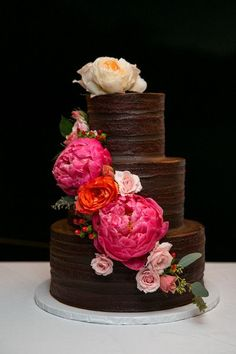 Unique chocolate wedding cake idea - three-tier chocolate frosted wedding cake with cascading hot pink peonies, red and blush roses  - beautiful! {Crown Images photography by Sage}