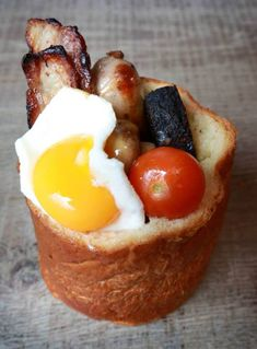 - an individually baked brioche loaf which is hollowed out and filled with sausage, lean bacon, tomatoes, mushrooms, spicy baked beans, black pudding and topped with an egg,