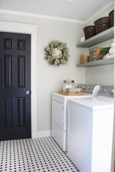 Gorgeous Neutral Laundry Room... love the black door and craftsman style casing, floating shelves, baskets, love love love!