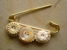 brooch with buttons and lace.  Hmmm...small amount of crochet edging to fit desired pin, attach buttons ~ do-able!