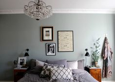 I like how the fussiness of the chandelier (in a bedroom!) is offset by the maidenhair fern. I also like that the pretty robe has its own place on the wall. Oh, and that wall walks on a fence between eggshell and grey cement.