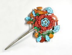 Mandchu hairpin richly adorned with pieces of coral, amber, jadeite and kingfisher feathers to compose a flower motif. They are mounted in three dimensions. These different materials are supposed to bring good fortune to the wearer.China