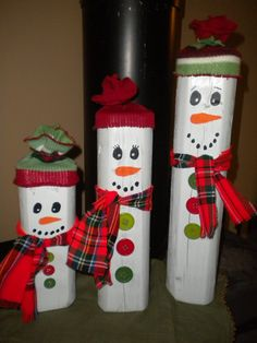 Country Christmas Snowmen made from landscape timber pieces. Knit hats, flannel scarves and plastic buttons.