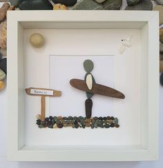 A beautiful and unique handmade beach pebble picture of person going to the beach holding a driftwood surf board, with driftwood Beach or Traeth sign with seagull flying overhead. This picture would compliment any room and would make a perfect gift. The picture is made using pebbles, driftwood, shell, driftwood and card. All materials are carefully placed and fixed with high strength glue onto high quality white linen card. I can include printed quotes or personalised messages onto picture…