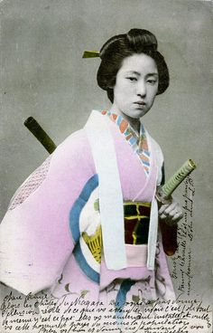 Katana Odori 1906    A woman with a katana (sword) at her side and a wooden or bamboo shaft of another implement on her back.    Although, I initally thought that she might be a woman of the Samurai Class, after further research I think that she is in fact a dancer, probably a Geiko (Geisha), dressed to perform the Katana Odori (sword-dance).