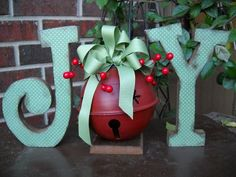 JOY with a Bell    letter set-UNFINISHED. $5.00, via Etsy or use the large craft letters found at Hobby Lobby and cover with fabric or scrapbook paper.  Antique if desired.  Use a large bell, spray paint it to the desired color, and then antique it.  Glue to a wooden base and then add bow and berry stems.