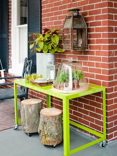 Love versatile furnishings! A simple desk on casters (painted citrus green!! CUTE!) can be moved around the porch for dining, gardening projects and display {and those stump stools are fun too!}