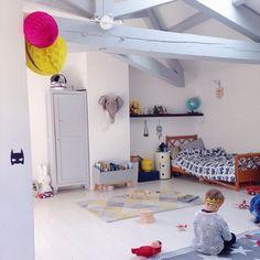 Chambre d'enfant aménagée dans les combles avec poutres peintes en gris bleu