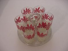 MID CENTURY SET OF 6 DRINKING GLASSES W/CENTER HANDLED ROUND GLASS CADDY