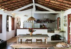 O telhado em duas águas, com tesouras aparentes, cobre a área social e a cozinha com fogão a lenha  Marcos Antonio / Casa e Jardim