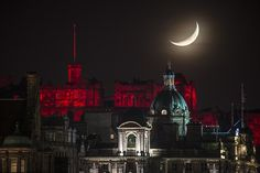 The sky at night: A thin crescent moon sets over Edinburgh Castle on Christmas Day 2014 in...