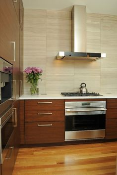 Contemporary Kitchen with sleek sculptural hood and brown cabinet's