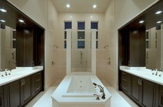 Naples Luxury Home Blog - contrast transitional bathroom - walk through glass shower - soaking tub - his and hers vanities