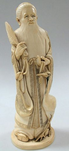 A Japanese carved ivory okimino figure, of a long bearded sage holding a leaf fan, standing aside and tempting a stork, signed Gyokuzan to a red inset seal, Meiji period, c.1900, 34.5cm high.