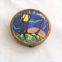 THE COMPACT IS MADE OF BRASS METAL AND MEASURES APPROX. 5 CMS IN DIAMETER. THE LID FEATURES A SYTLISED NIGHT TIME FOREST SCENE WITH THE MOON BEHIND THE TREES AND GREEN BIRDS IN FLIGHT. THE PICTURE IS PROTECTED UNDER A CELLULOID DISC COVERING. | eBay!