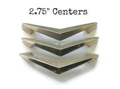 This listing is for 3 great, vintage chevron drawer pulls with all 6 screws -These have a pale brass colored metal patina and are in good condition with some finish wear. These are very barely brass, close to chrome colored. Shown in the 4th picture next to a bright brass and a true chrome pull. -These are nice vintage pulls that will add character and authenticity to your project! -Measurements: Just over 3.5 wide, about 7/8 tall, with 2.75 centers (from the center of one hole to the ce...