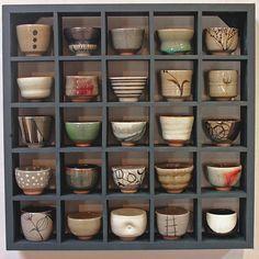 Teas or tea cups in a grid shelf.