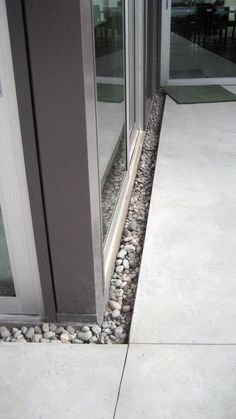 Trench-drain-between-sliding-door-and-concrete-slab-0-filled-with-river-rock-3
