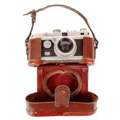 """1930's Foca 35mm camera from France with leather case. Decorative purposes only.  Product: Camera and caseConstruction Material: MetalColor: Black and silverFeatures:  Made in FranceFor decorative purposes only Dimensions: 3.5"""" H x 6"""" W x 2.5"""" D (case)Note: Due to the vintage nature of this product, minor wear and tear is to be expected. Products may show signs of brand marks, scrapes or other blemishes."""