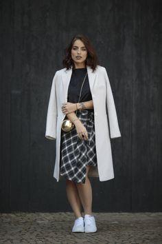Look da Bruna Unzueta na SPFW, com saia midi xadrez, sobretudo e tênis branco.