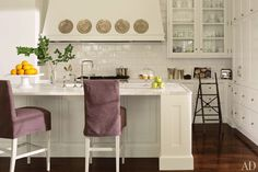"""White sets such a beautiful tone,"" says decorator Suzanne Kasler of the color scheme she used in her refined Atlanta home, which she renovated with residential designer William T. Baker. The tile is by Waterworks, and the barstools are from Kasler's line for Hickory Chair. Glass-front cabinets display tableware, while an adjacent wall of storage keeps other items out of sight. (April 2012)"