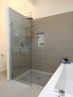 Pure white caeserstone tub surround, hansgrohe metris faucet, glass mosaic tile (Daltile - City lights), taupe 12 x 24 porcelain floor (tierra Sol, English bay collection), shower glass panel, shower niche, rain shower head, wet bath. :: Design by ID by Gwen